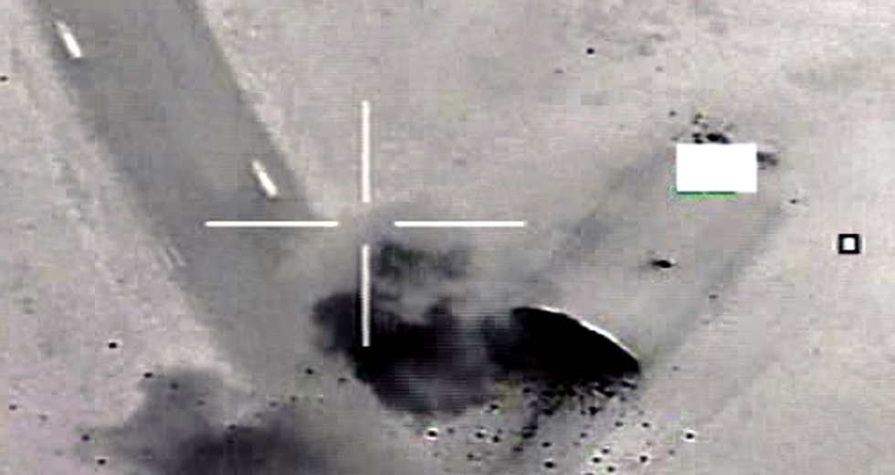 Image of fighter jet bombing air craft shelter in Libya